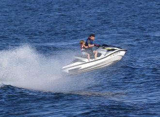 Man and child riding on a seadoo at a lake