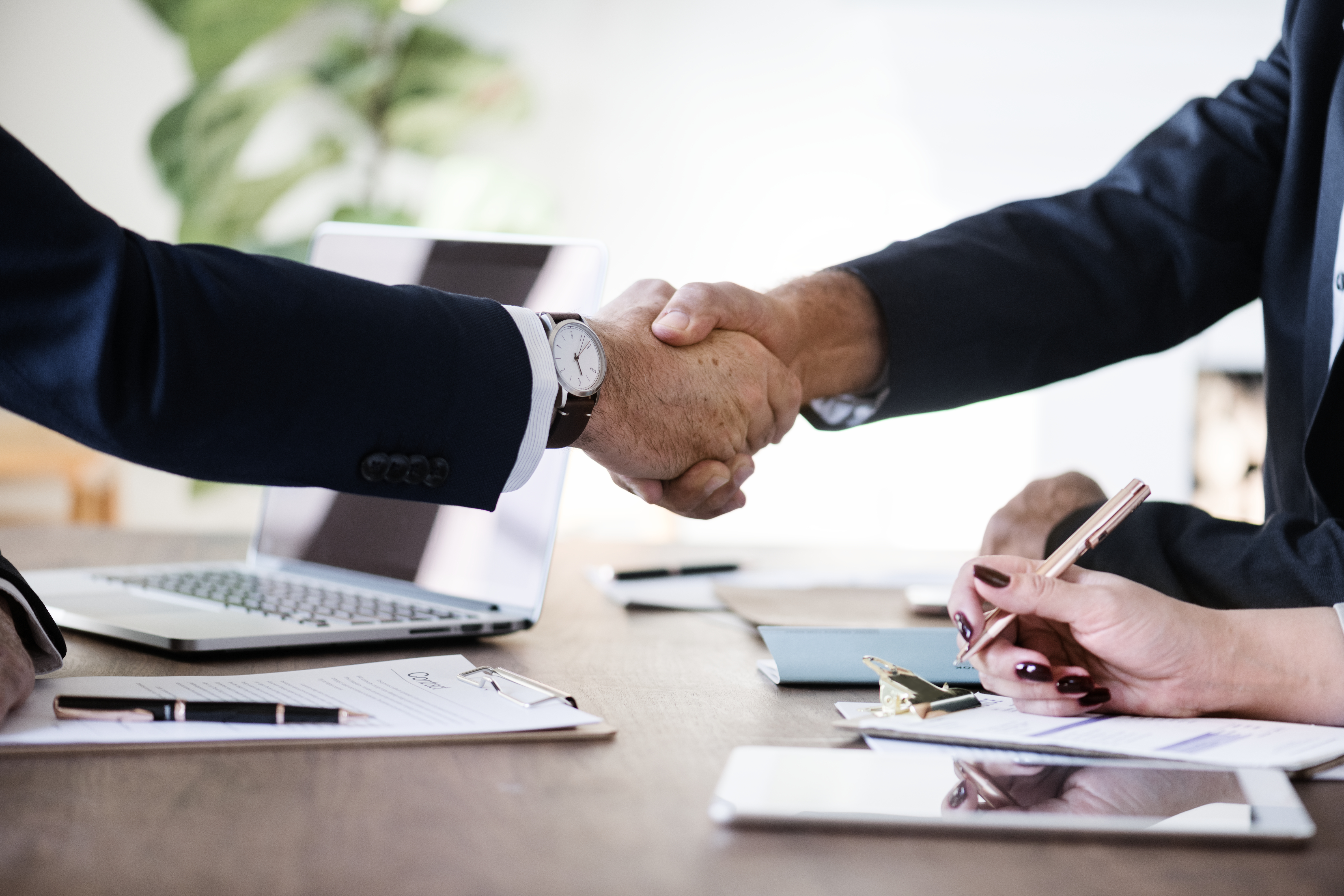 Two people in business attire shaking hands over a wooden table covered with documents, clipboards, and electronic devices