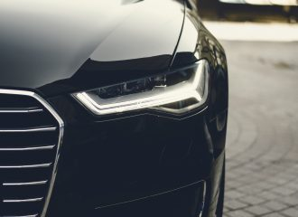 a close up of a black auto's grill and left headlight