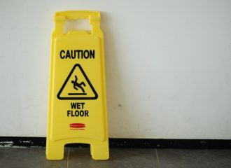 a wet floor sign propped up against a wall