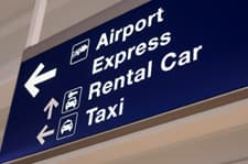 airport sign with directions to the airport express area, the rental car area, and the taxi area