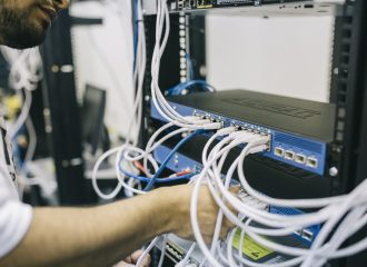 an IT professional plugging an ethernet cable into a network switch