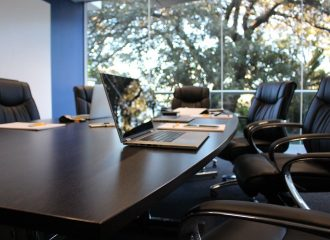 black leather chairs around a wooden conference desk that has laptops and notepads sitting on it
