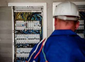 electrician standing in front of two open circuit breaker boxes