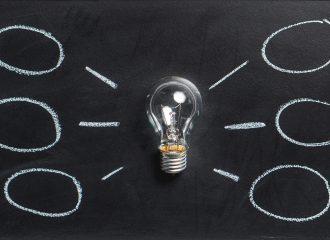 lightbulb laying on chalkboard with mind map drawn around it