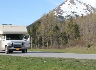 rv parked on the road in front of a mountain