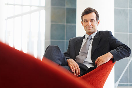 smiling man in business suit sitting cross-legged in chair