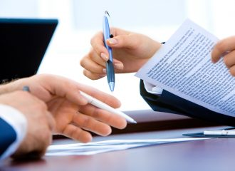 two businesspeople going over documents while holding pens