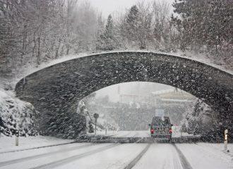 van driving under overpass in winter weather