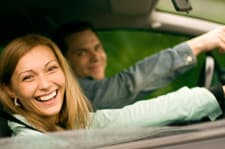 woman and man smiling while sitting in car