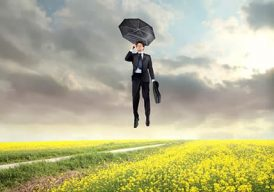 a man hovering over a field with an umbrella