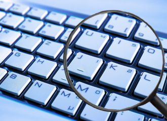 a person holding a magnifying glass over top of a keyboard
