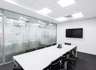 a brightly lit conference room with a table, phone, chairs, and a television