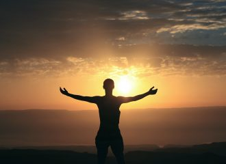 a person standing with their arms wide open, facing a sunrise