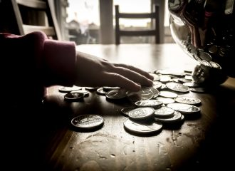 child grabbing coins from table next to piggy bank