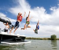 children jumping off of a boat into a lake