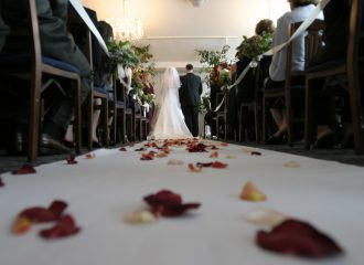 ground view of wedding aisle with bride and groom at altar