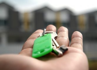 house keys in the palm of a person's hand, with homes in the background