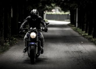 person in riding gear driving motorcycle down country road