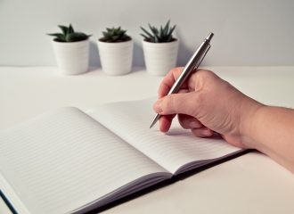 person writing in notebook with pen