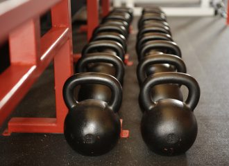 row of barbells sitting on the floor of a fitness club