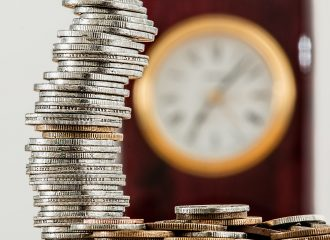 stack of coins with clock in background